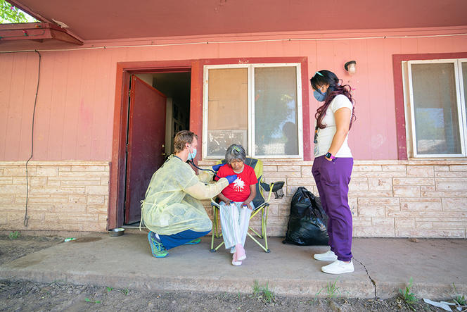 Dr. Ryan Close, left, an Indian Health Services physician, and J.T. Nashio, right, a community health worker, check on Judie Declay, who lives on the Fort Apache Indian Reservation in Arizona, on July 8, 2020.  (Tomás Karmelo Amaya/The New York Times)
